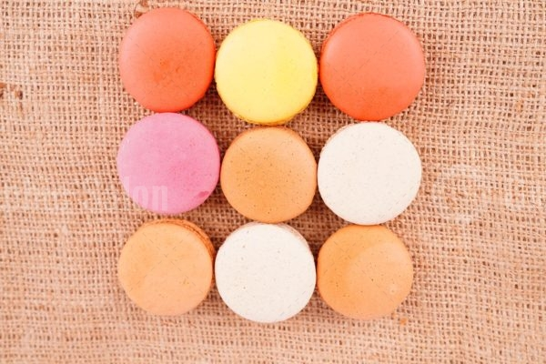 Top view assorted colorful macaroons on burlap
