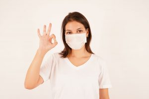 Girl in medical mask showing OK gesture